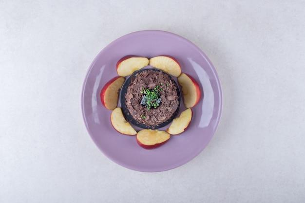 대리석에 접시에 브라우니 케이크와 얇게 썬 사과.