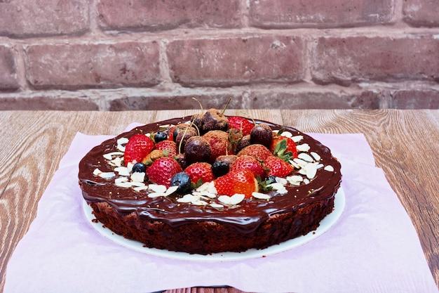 木製のテーブルに赤いベリーで飾られたブラウニーケーキ