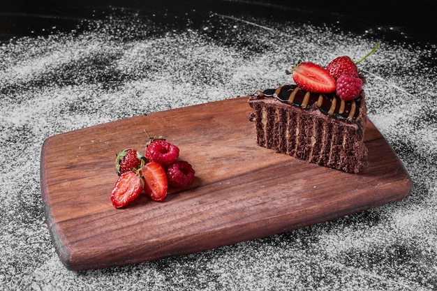 Brownie cake slice on a wooden platter .