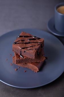 초콜릿 소스를 곁들인 브라우니 케이크. 수제 초콜릿 디저트. 인기있는 다크 초콜릿 케이크. 확대.
