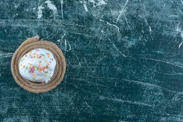 파란색 배경에 삼발이에 크림 브라우니 케이크. 고품질 사진