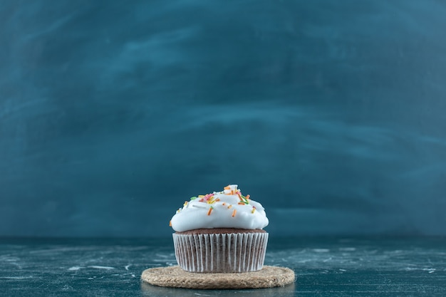 Brownie cakes with cream on a trivet , on the blue background. high quality photo