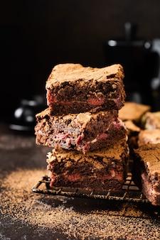 暗い背景にチェリーとチョコレートのブラウニーチーズケーキケーキ。セレクティブフォーカス。
