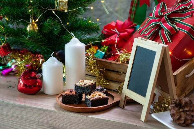 Brownie chocolate cake on wooden table, with christmas decoration background