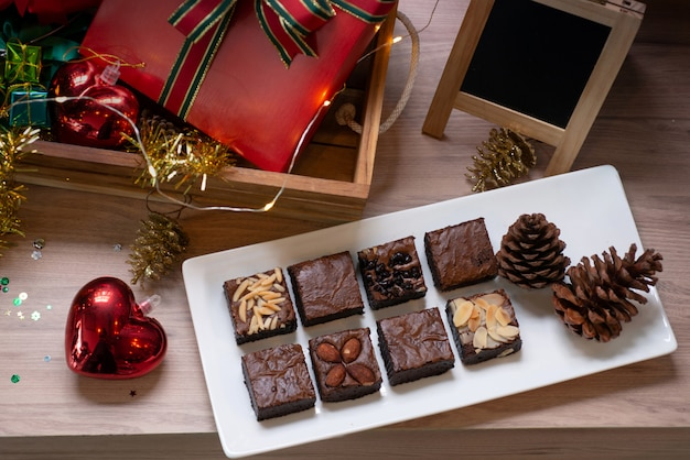 Brownie chocolate cake on a wooden table, with christmas decoration background