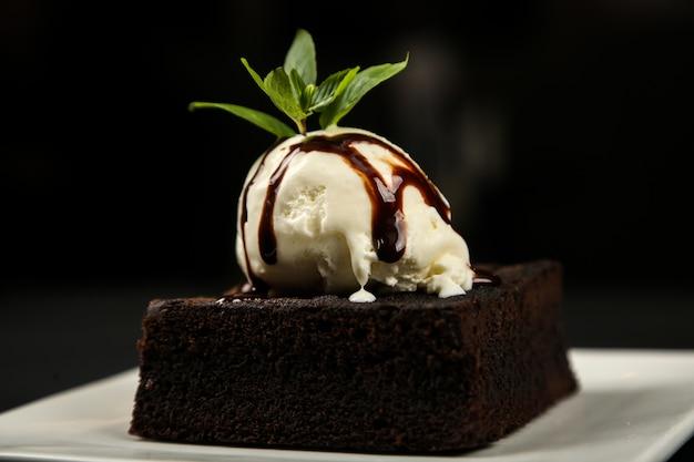 Брауни, шоколадное мороженое, мятный сахарный порошок, вид сбоку