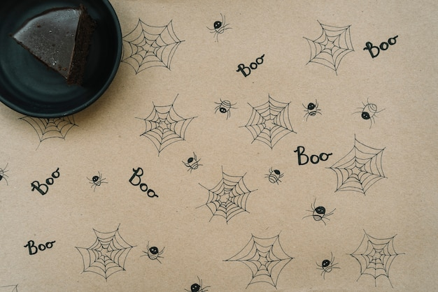 Brownie standing paper with funny drawings of spiders and webs