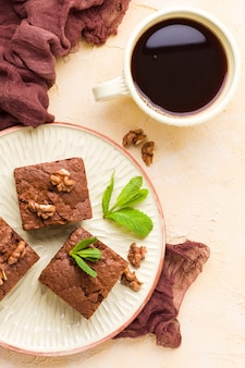 Brownie sweet chocolate dessert with walnuts and meant leaves on craft plate and cup of black coffee