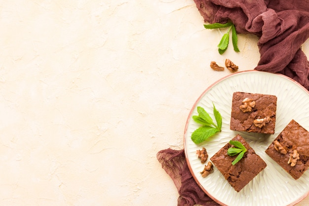 Brownie sweet chocolate dessert with walnuts and meant leaves on craft plate with copy space.