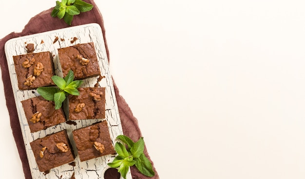 Brownie sweet chocolate dessert with walnuts and meant leaves on retro board
