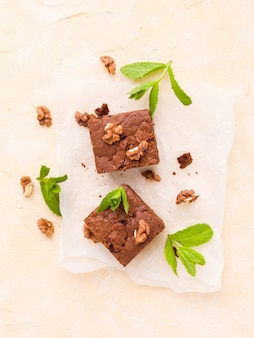 Brownie sweet chocolate dessert with walnuts and meant leaves on white paper with copy space.