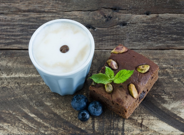 Brownie with fruits and glass of coffee.