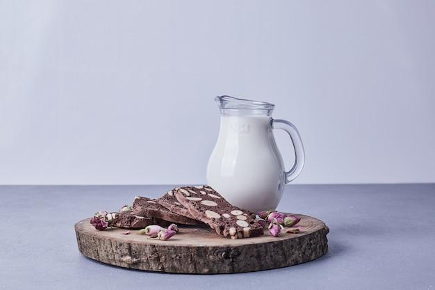 Брауни с орехами подается с банкой молока на деревянном блюде.