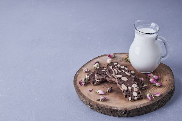 Brownie with nuts served with a jar of milk.