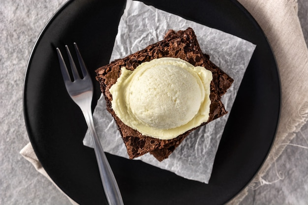 Brownie with vanilla ice cream scoop on gray stone table