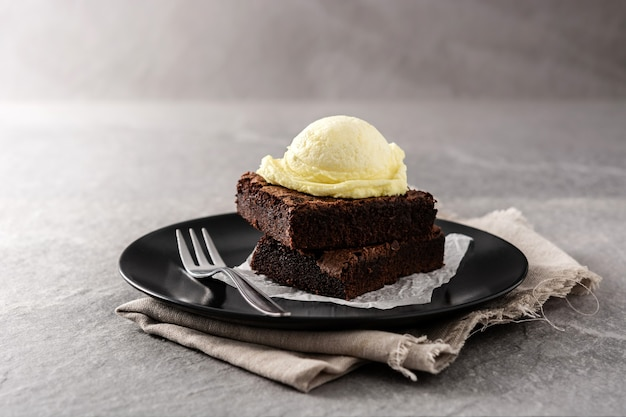 Brownie with vanilla ice cream scoop on gray stone