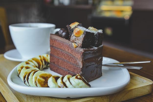 브라우니 초콜릿 케이크와 실내 아침 조명이있는 따뜻한 차.