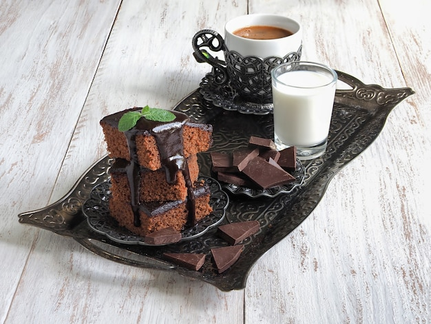 Brownies on a tray with milk and a cup of oriental coffee
