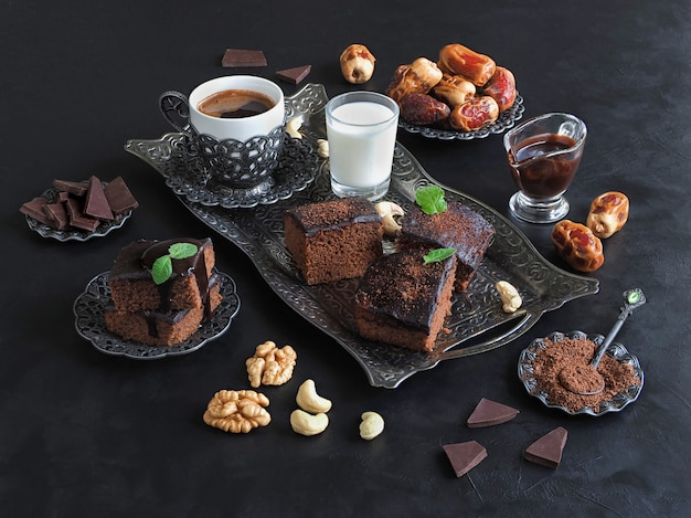 Brownies with dates, milk and coffee are laid out on a black surface. festive ramadan background
