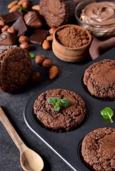 Brownies with nuts and chocolate on a black background