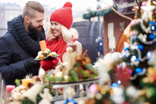 クリスマスマーケットでいくつかのクリスマスオーナメントを閲覧する