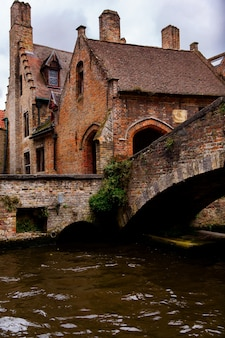Брюгге, фландрия, бельгия, европа - 1 октября 2019 года. средневековые древние дома из старых кирпичей и водные каналы в брюгге (брюгге), провинция западная фландрия, бельгия.