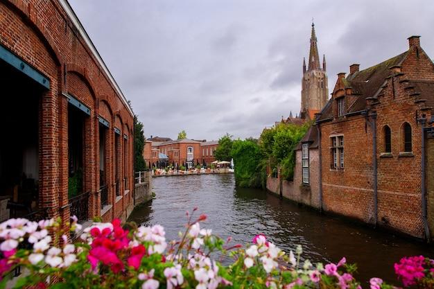 Брюгге, фландрия, бельгия, европа - 1 октября 2019 года. средневековые старинные дома из старых кирпичей и водные каналы на древней средневековой улице в брюгге (брюгге)