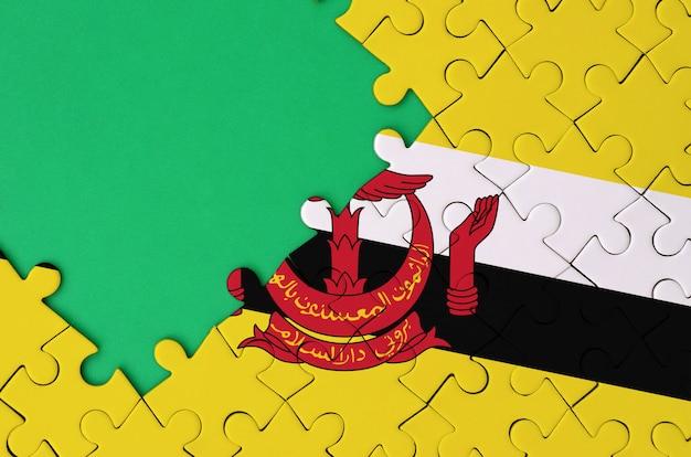 브루나이 다루 살람 국기는 왼쪽에 무료 녹색 복사 공간이있는 완성 된 직소 퍼즐에 그려져 있습니다.