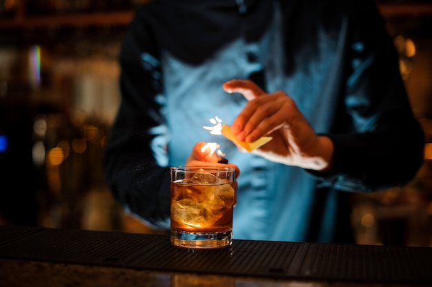 Brunet bartender serving a fresh alcoholic cocktail with a smoky note