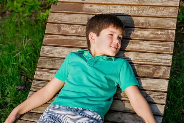 티셔츠를 입은 8세의 브루넷 소년은 푸른 잔디를 배경으로 햇볕에 나무 데크 의자에 누워 있습니다. 편안하고 게으른 자세의 소년은 눈을 감았다.