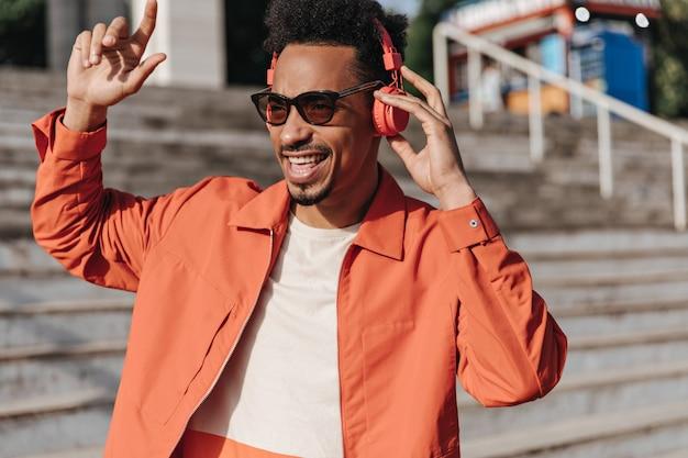 선글라스, 주황색 재킷 및 흰색 티셔츠를 입은 매력적인 검은 피부의 brunet 남자가 노래하고 외부의 빨간색 헤드폰으로 음악을 듣는다.
