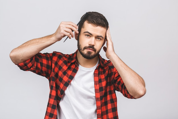 Brunet man combing his hair with hairbrush, holding hand on head, isolated on white background.