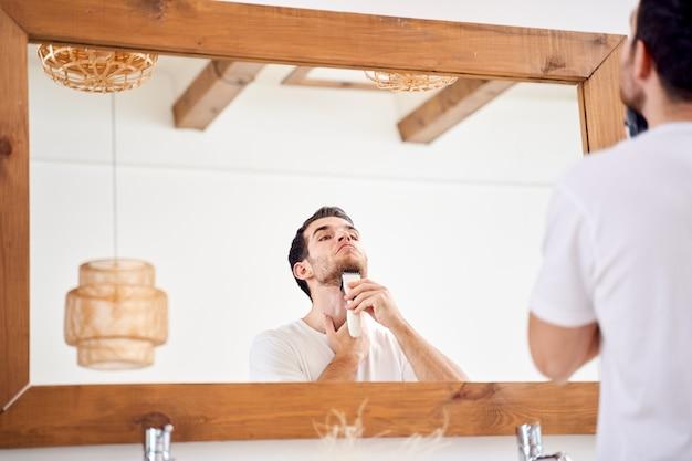 Брюнет мужчина в белой футболке бреется, стоя возле зеркала в ванне утром