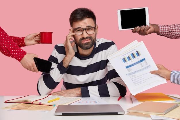 ガジェットと書類に囲まれた机に座っている黒髪の男