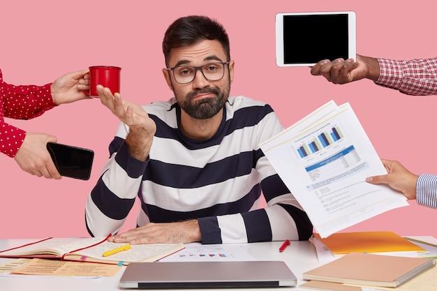 가제트와 서류로 둘러싸인 책상에 앉아 검은 머리 남자