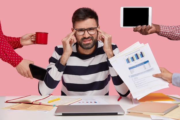 Brunet man sitting at desk surrounded with gadgets and papers