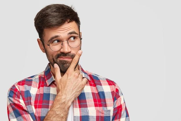 Brunet man wearing round eyeglasses and colorful shirt