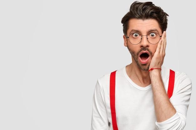 丸いメガネと白いシャツを着たブルネットの男