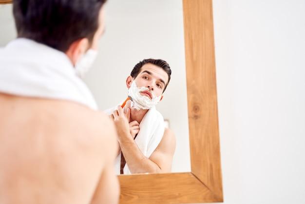 Брюнет мужчина с пеной на бороде бреется возле зеркала утром