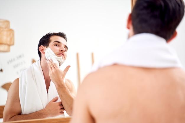 Брюнет мужчина с полотенцем на плечах намазывает лицо пеной для бритья, стоя в ванне возле зеркала