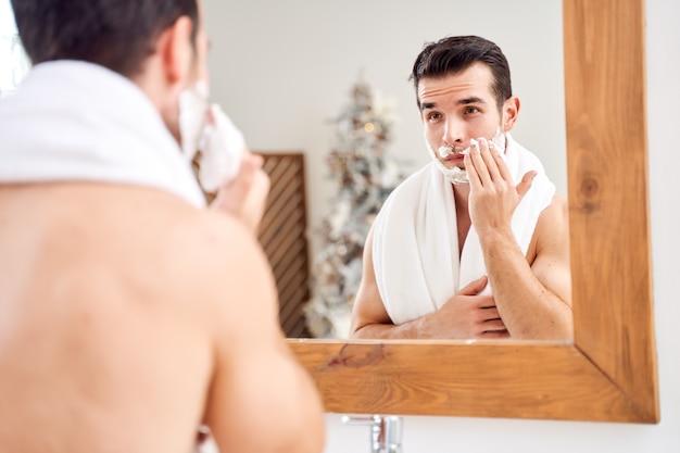 Брюнет с полотенцем на плечах намазывает лицо пеной для бритья, стоя в ванне возле зеркала