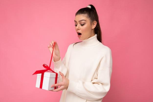 Брюнетка женщина изолирована на стене красочного фона в модном наряде смотрит с подарочной коробкой