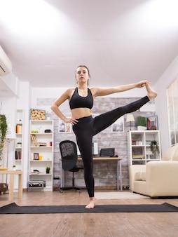 Bruna donna adulta che fa una posa di yoga gamba in piedi nel soggiorno.