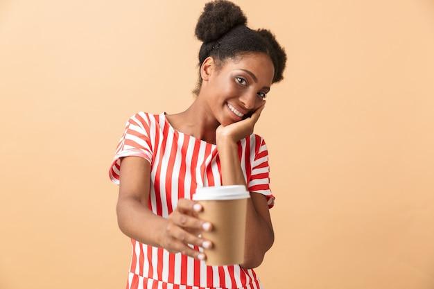 持ち帰り用コーヒーと紙コップを保持しているカジュアルな服装のブルネットのアフリカ系アメリカ人女性、
