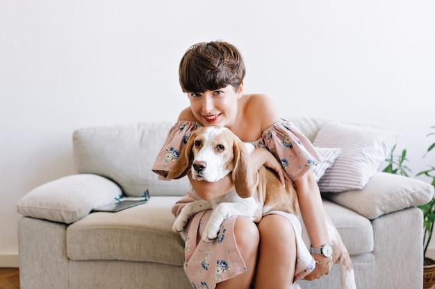 ブルネットの面白がって女性は彼女の膝に大きな子犬を保持し、笑顔で花飾りの腕時計とドレスを着ています