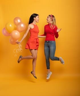 ブルネットとブロンドの女の子は風船でパーティーの準備ができています