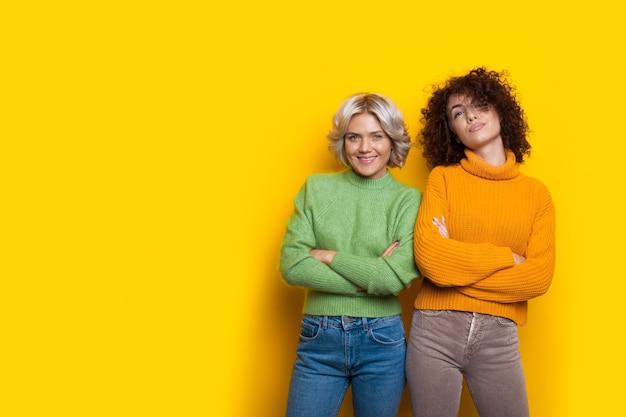 Брюнетки и блондинки позируют со скрещенными руками на желтой стене, рекламируя что-то
