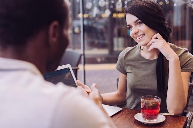 남자를보고 그녀의 얼굴을 만지고있는 동안 웃 고 갈색 머리 매력적인 예쁜 여자