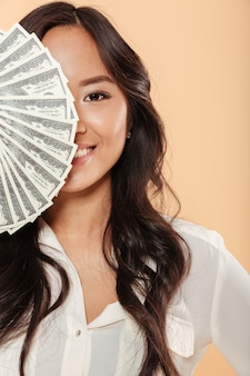 Brunette asian female smiling and covering half of her face with fan of 100 dollar bills being successful businesswoman over peach background