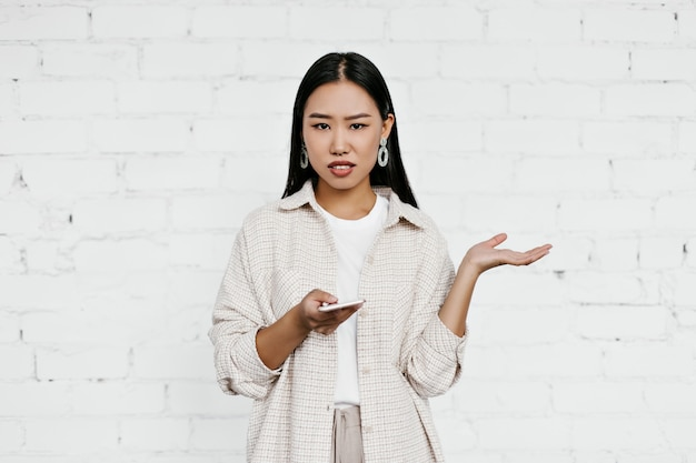 Brunette asian woman in disbelief looks at camera on white brick wall wall